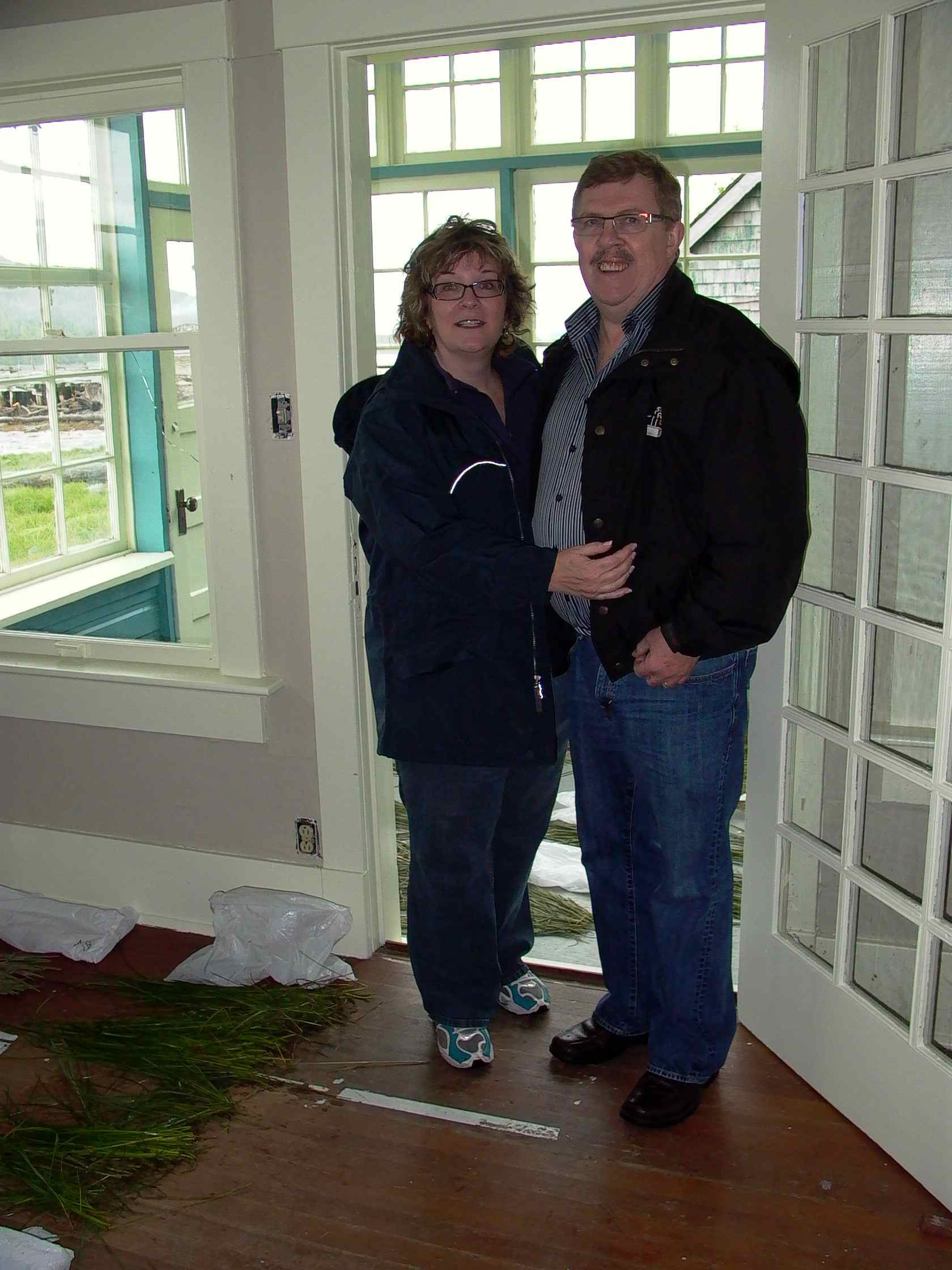 Cassiar Cannery: Rod Breen with his wife Brenda standing in the living room of his aunt and uncle's house who were Ewen and Kathryn Macmillan - the principles of Cassiar Packing Company for many decades.