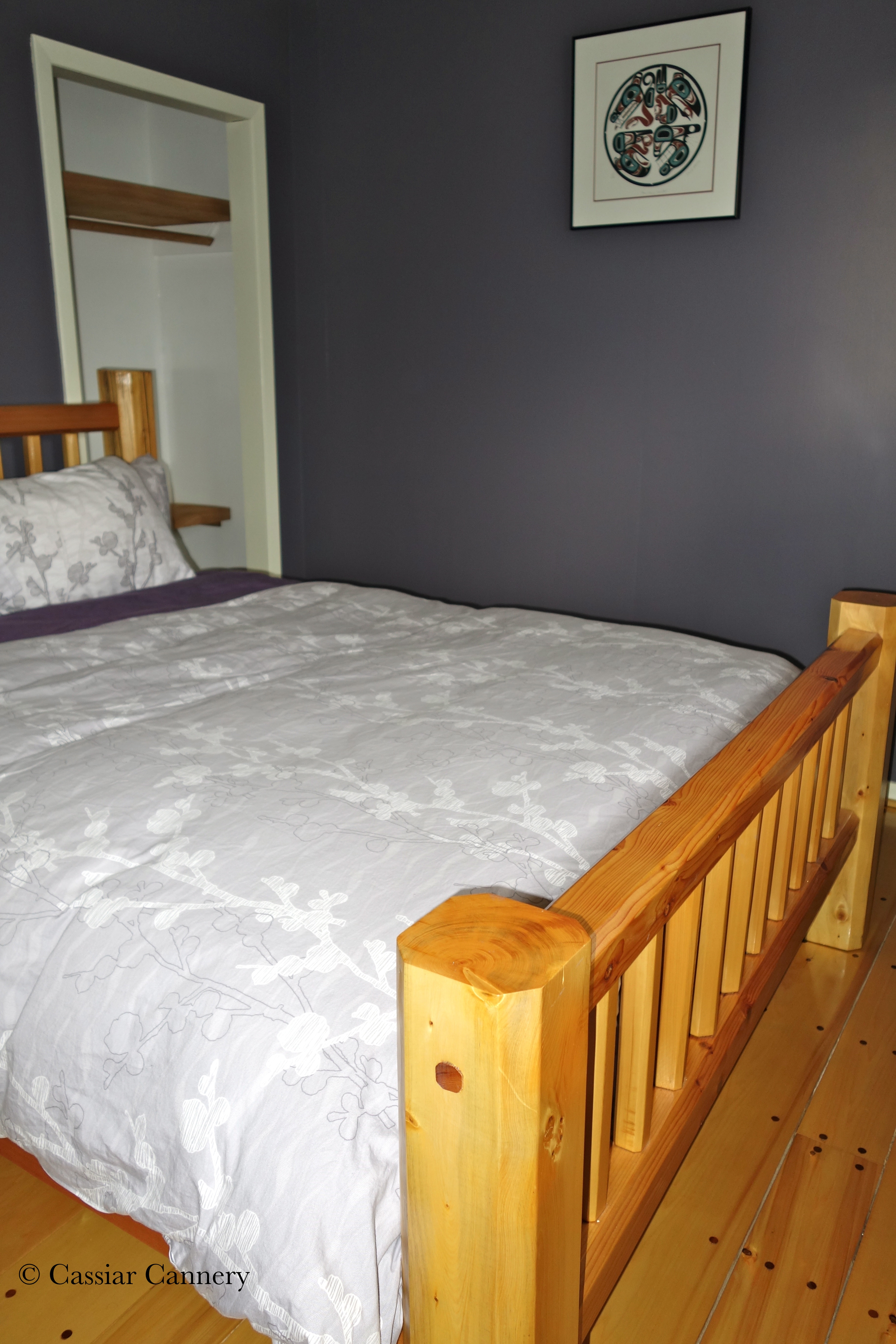 Cassiar Cannery - Steelhead House - reclaimed cedar queen bed in the front room with luxury bedding